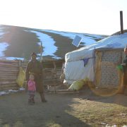 Mongolian husband, wife and child outside their family yurt