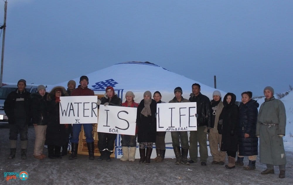 """""""water is life"""" sign being held up by a community of mongolian people"""