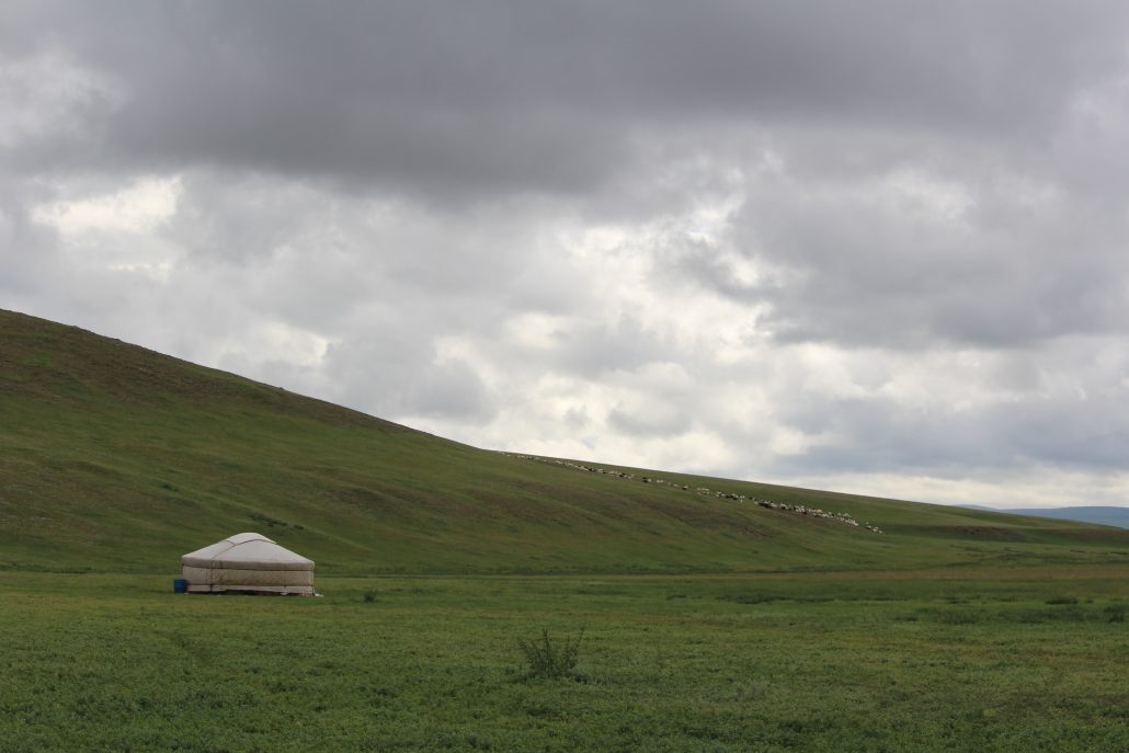 a mongolian yurt sitting alone in a vast valley