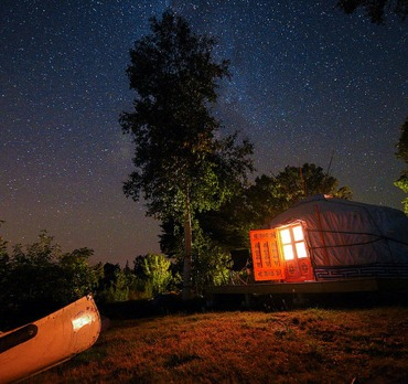night time yurt with lights on and a canoe out in front