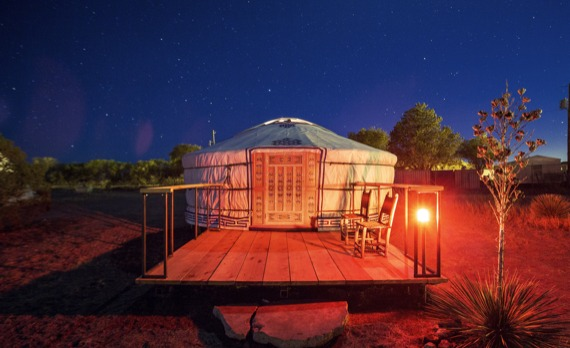 A GroovyYurt Yurt with a deck sits outside at night