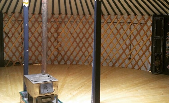 The inside of a yurt with a wooden stove
