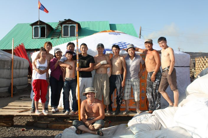a mongolian family posing in front of their yurt
