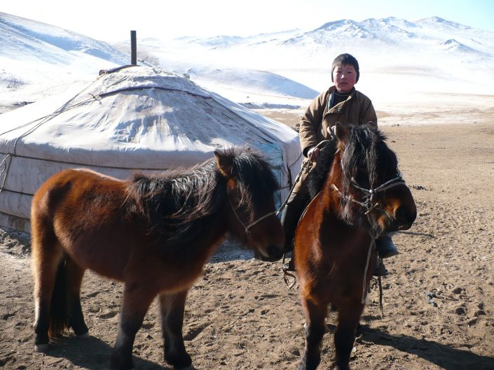 a young mongolian boy on a horse in front of his yurt