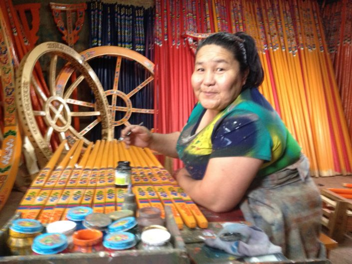 mongolian artist painting wood furniture by hand