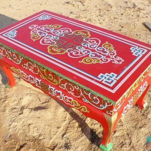 Ornate red curved legged table Groovy Yurts