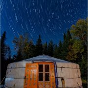Yurt at night with time-lapse of stars
