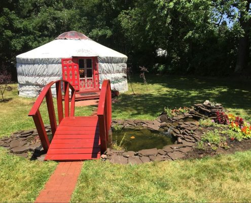 cozy Yurt in backyard with bridge over pond