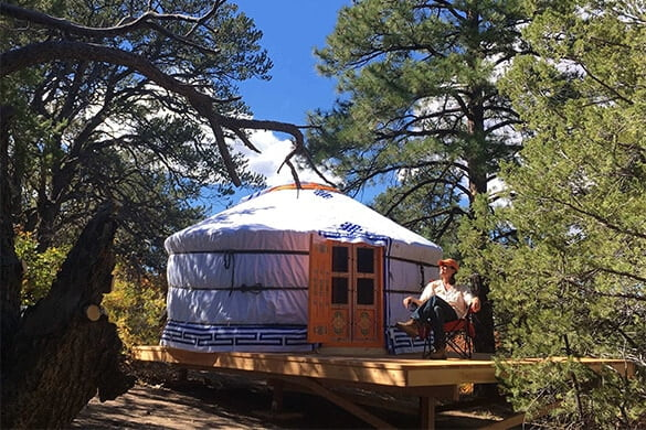 Man sits outside yurt in the woods