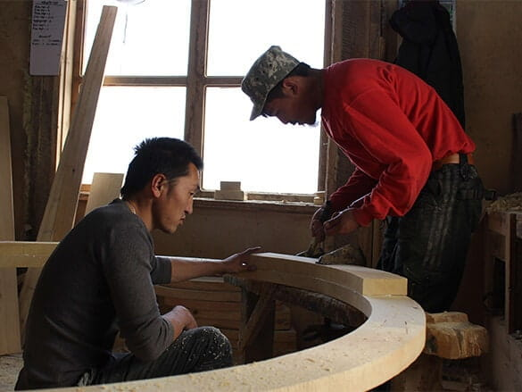 Two Mongolian carpenters working on yurt frame