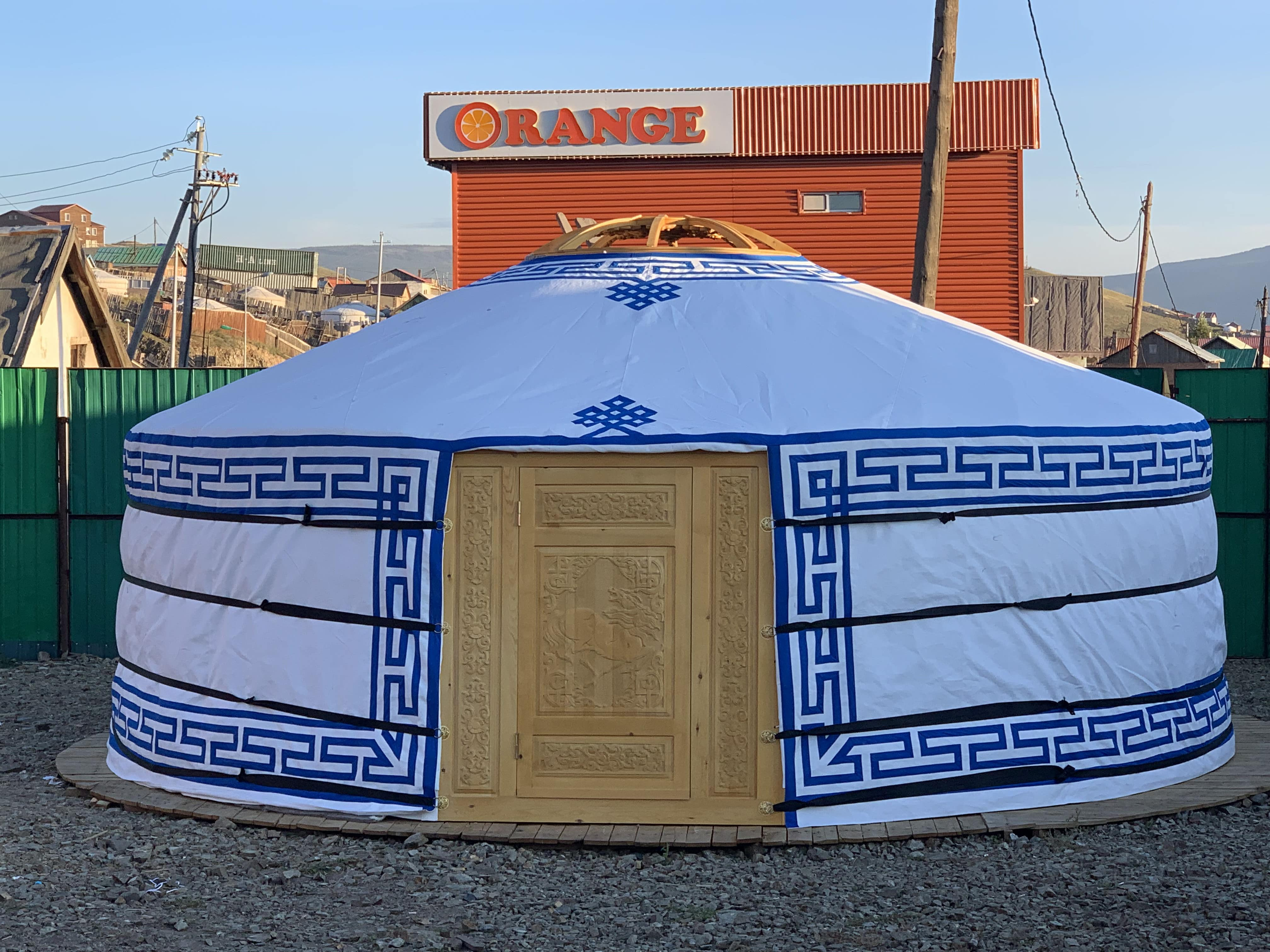 A beautiful yurt with a wooden door and blue borders