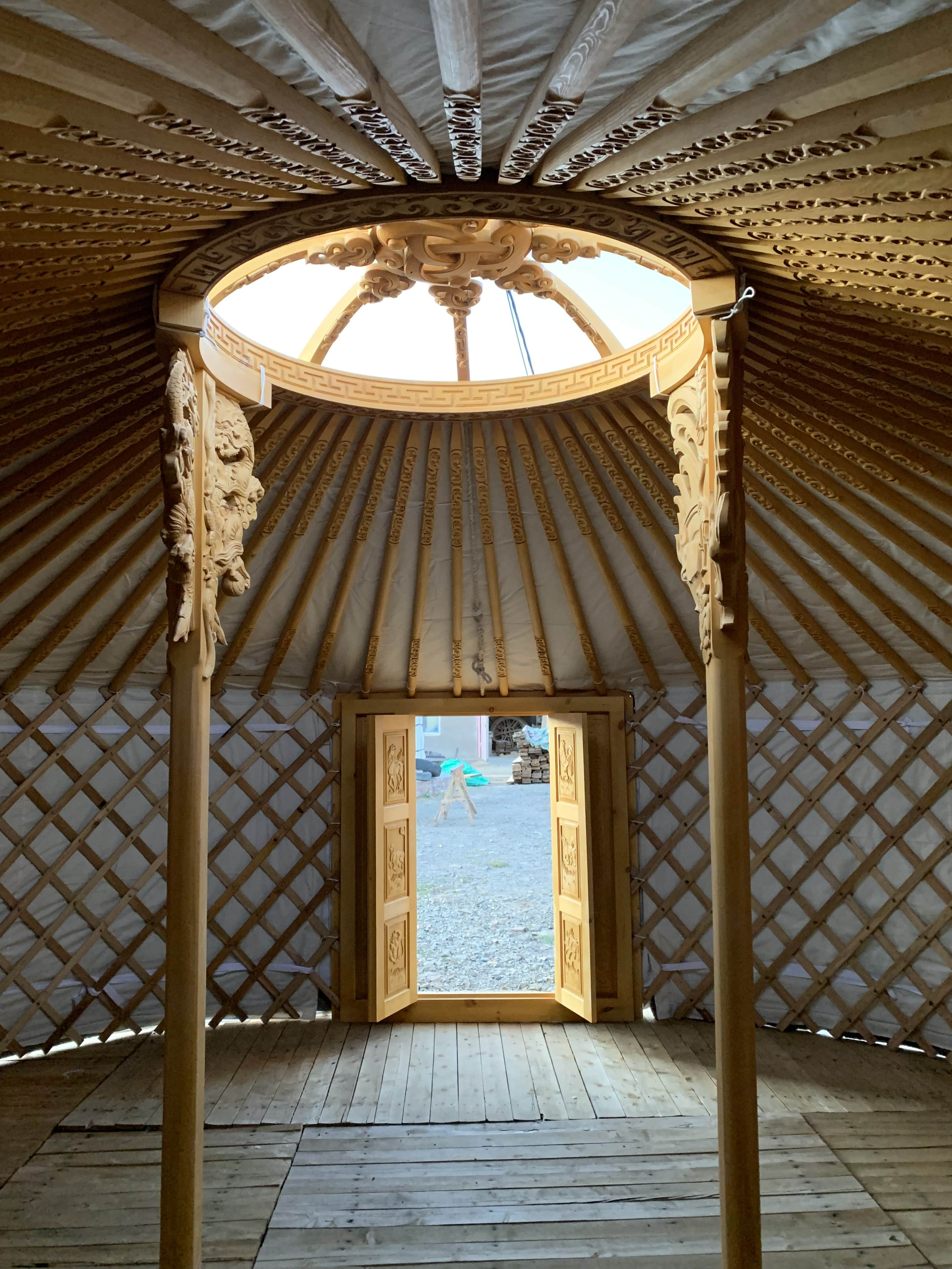 Inside a yurt with a finely carved roof