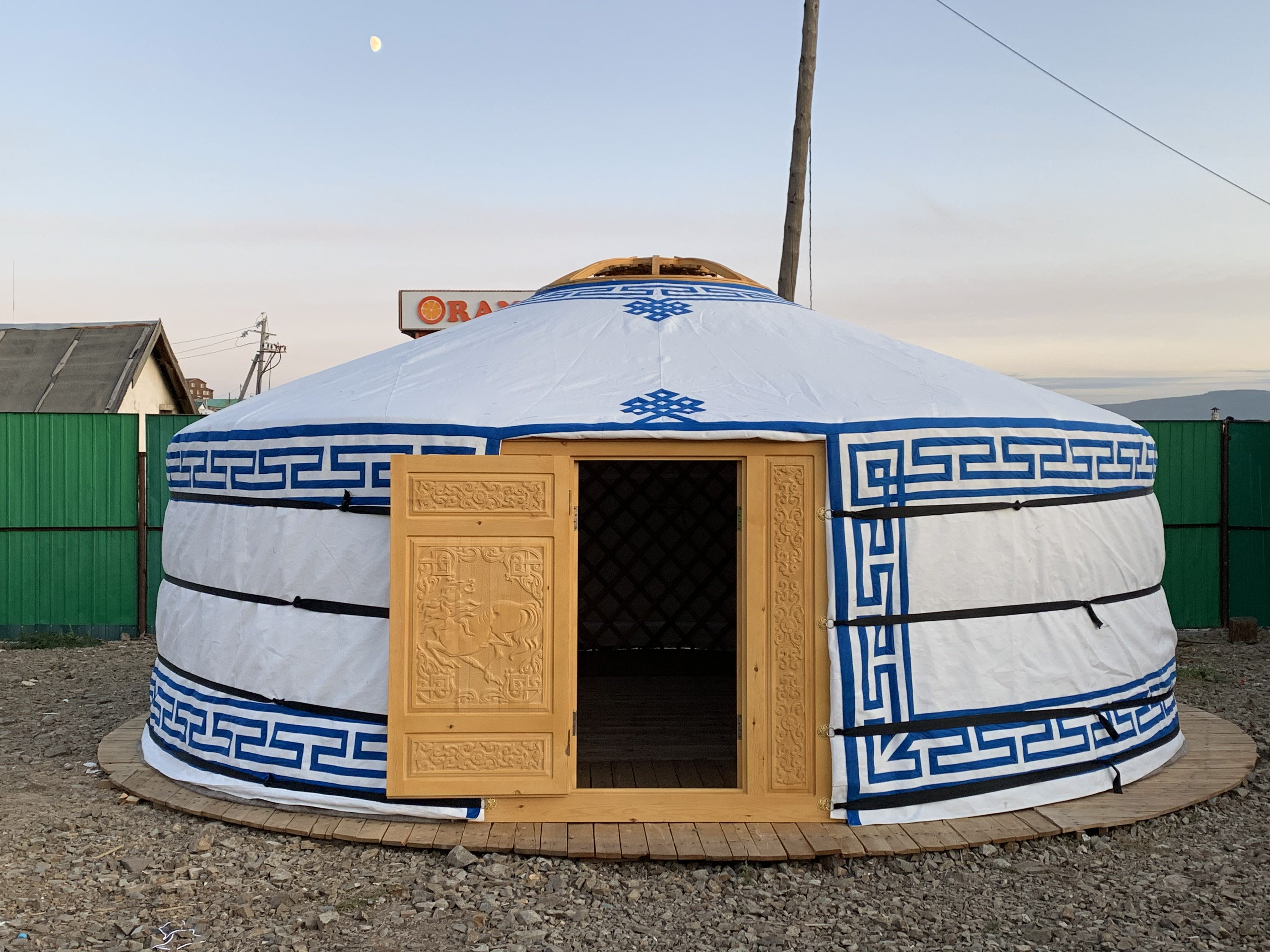 A yurt with a finely carved wooden door and blue accents