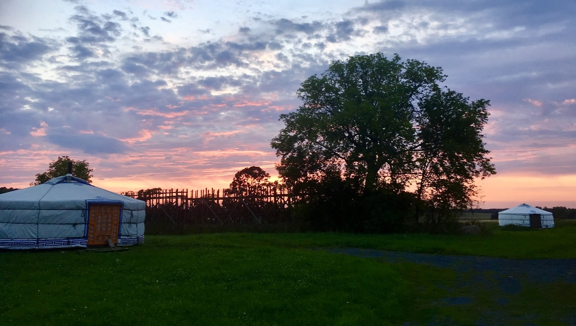 2 yurts set up in a camp ground during sunset
