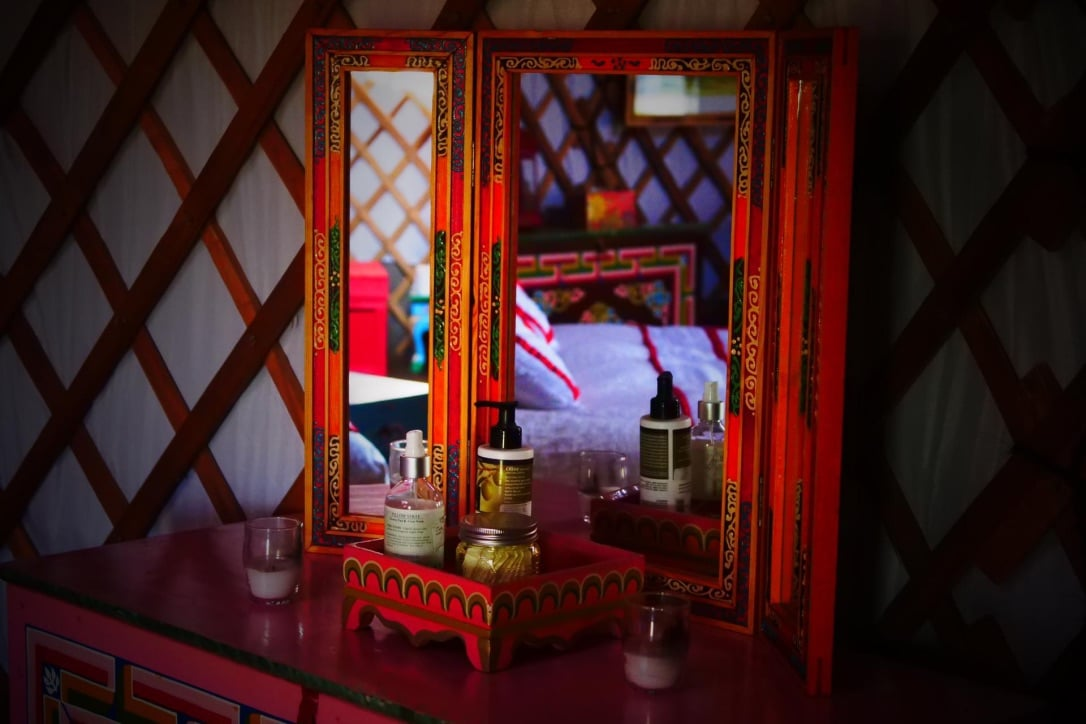 a dresser set up with a make up mirror station in yurt