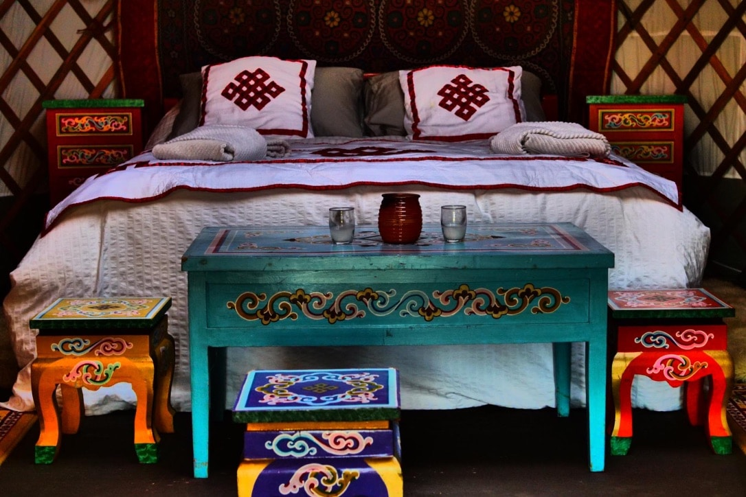 a bed, 2 night stands, table and 2 stools set up in a yurt