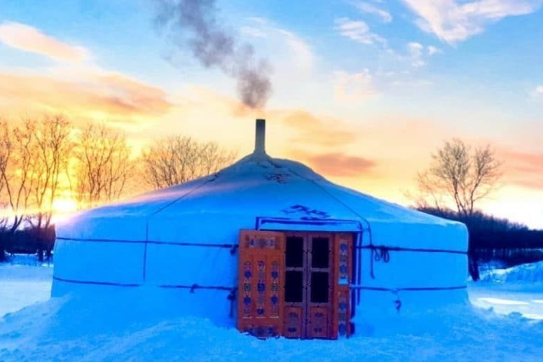 a smoking chimney of a yurt in the winter time