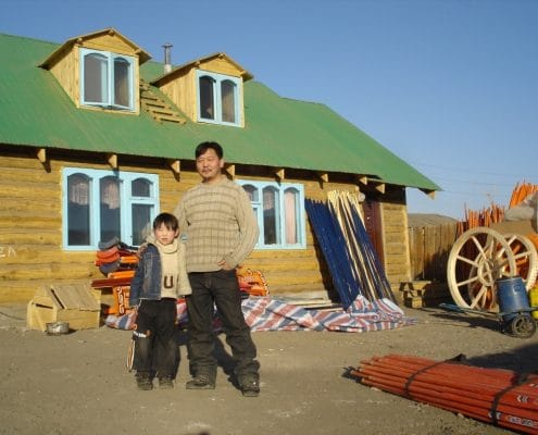 mongolian family in front of house