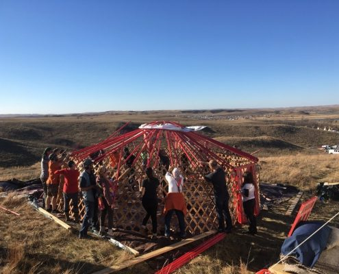 people assembling mongolian ger or yurt