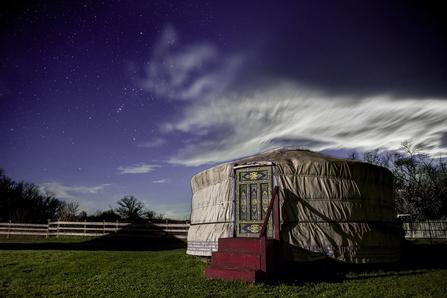 groovy yurt in the middle of a field at night