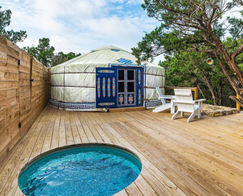 a yurt sitting on a deck with a hot tub nearby
