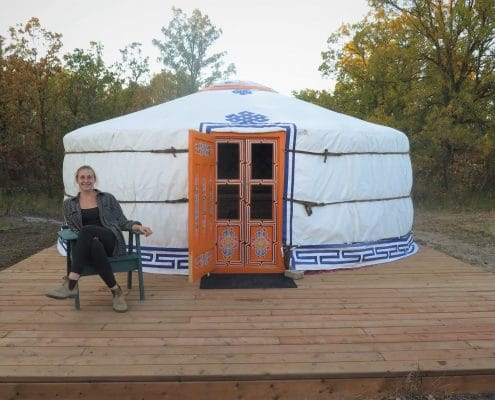 a happy customer sitting on a deck in front of their yurt