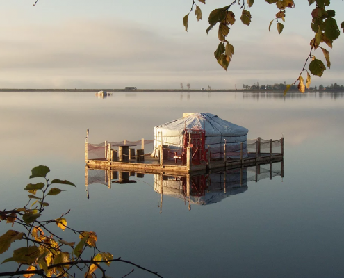 a groovy yurt set up on a floating down on a perfectly calm lake