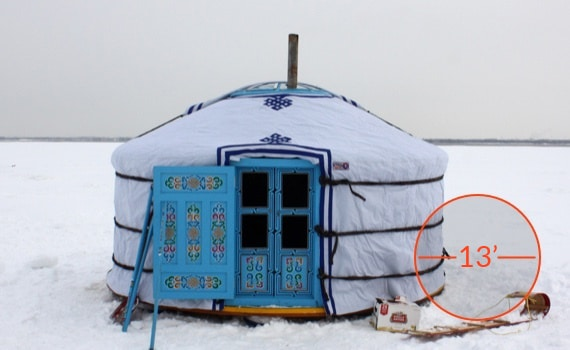 White 3 wall yurt with a sky blue door during winter.