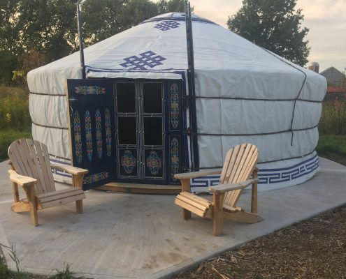 a white yurt with an inviting doorway and 2 muskoka chairs out front