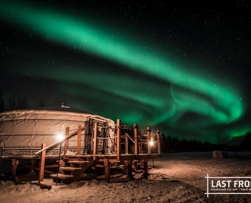 a yurt overlooking the northern lights on a winter day
