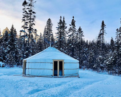 white yurt in the snow with smoke coming out of the chimney