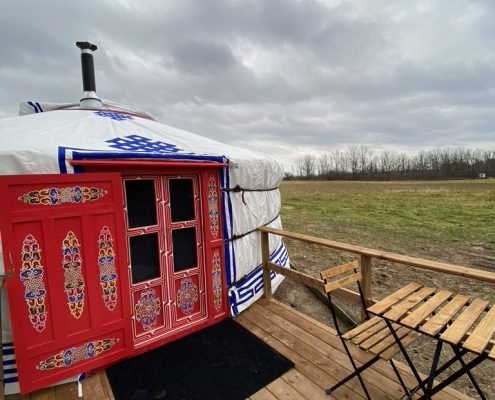 white yurt with a red door and a little sitting area out front