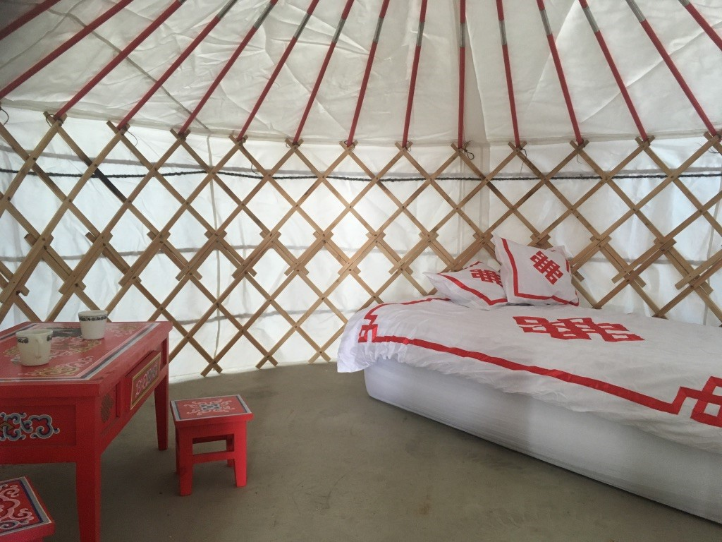bed and table inside a yurt