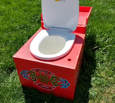 open humanure toilet sitting on the lawn beside a yurt