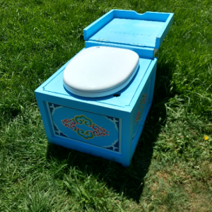 blue humanure toilet sitting on the lawn