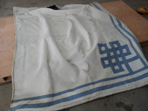 blue and white tarp with a rip in the side